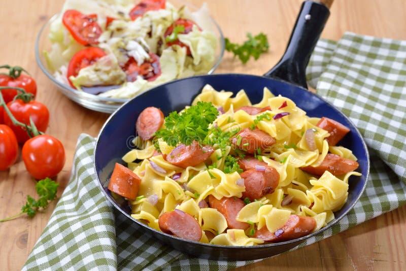 Austrian pasta dish with sausages stock photos