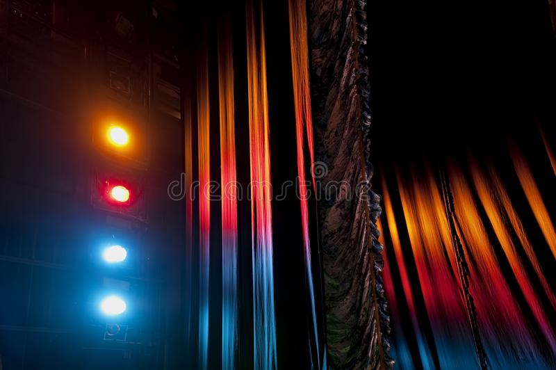 Austrian main front stage curtain under the light of stage floodlights. Austrian pleated main front stage curtain under the light of colorful stage floodlights stock images