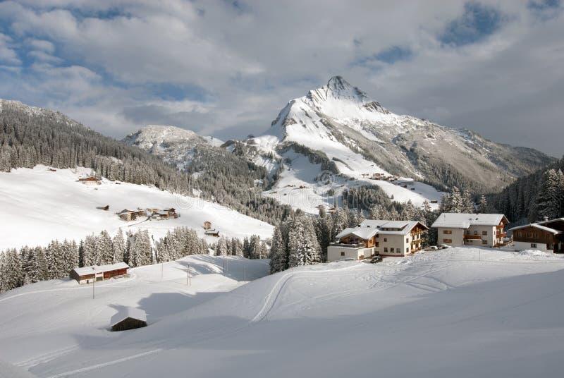 Austrian Winter Scene. Chalets in the village of Warth-Schrocken, and Mount Biberkopf, Warth am Alberg,Vorarlberg, Austria stock image