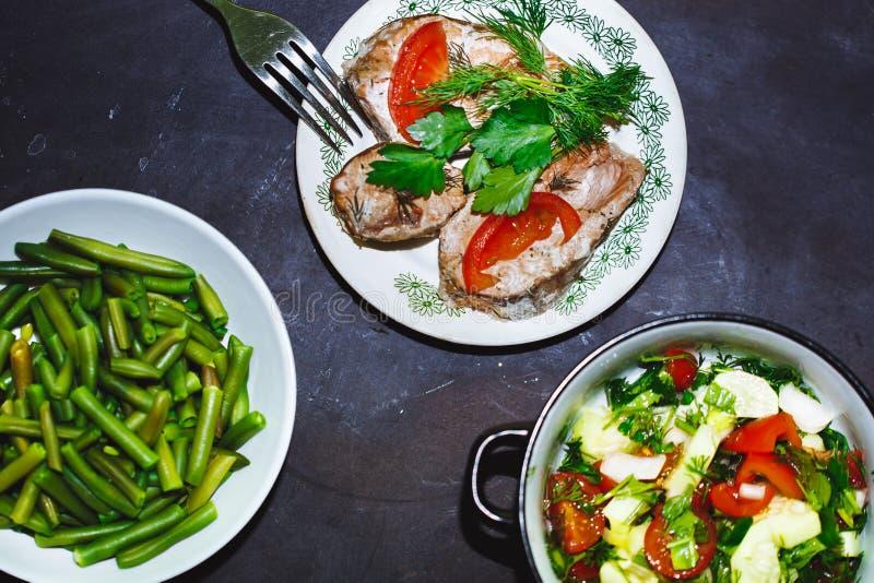 Auswahl des gesunden Lebensmittels auf einem schwarzen Hintergrund Stangenbohnen, Tomaten- und Gurkensalat, backten Fische lizenzfreie stockfotografie