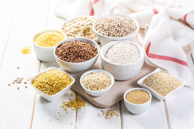 Auswahl von ganzen Körnern in den weißen Schüsseln - Reis, Hafer, Buchweizen, Bulgur, Brei, Gerste, Quinoa, Amarant, stockfotos