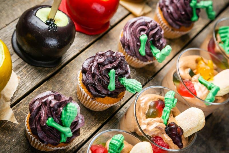 Auswahl von Halloween-Parteibonbons - Schokoladenkuchen, Karamelläpfel, kleine Kuchen, Schokoladencreme, Süßigkeiten stockfoto