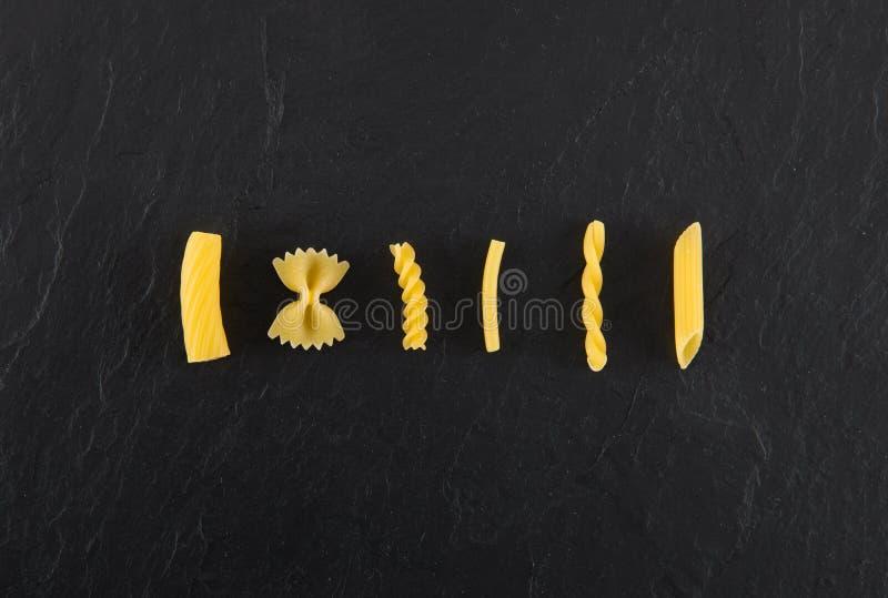 Auswahl von Teigwaren ungekocht, Isolat auf schwarzem Schieferhintergrund stockbilder