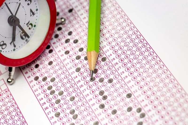 Auswertungsformular mit Bleistift und Wecker lizenzfreie stockbilder