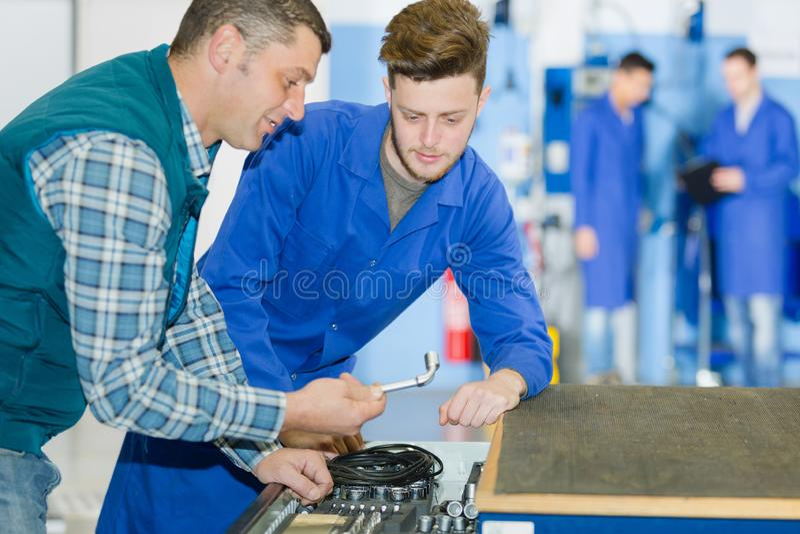 Auszubildende in der Automobilindustrie, die an Automobil-Motoren arbeiten lizenzfreies stockfoto