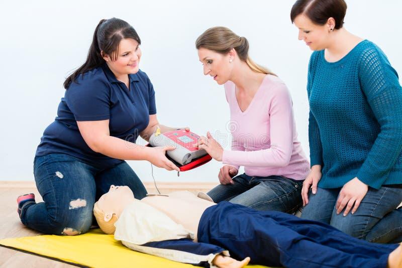 Auszubildende der ersten Hilfe, die lernen, Defibrillator für Reanimation zu benutzen stockbilder