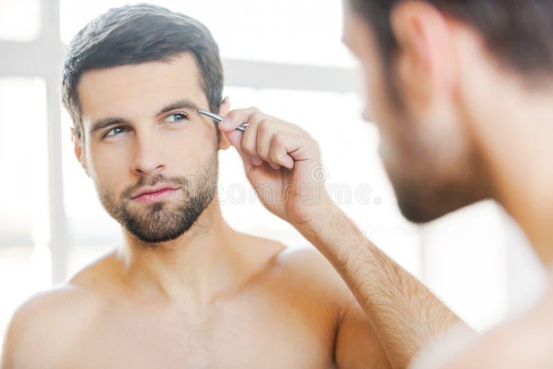 Auszupfen seiner Augenbrauen lizenzfreies stockfoto