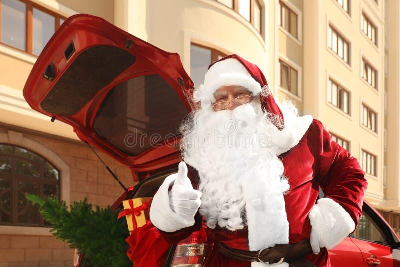 Auténtico Papá Noel cerca del auto con árbol de abeto y bolsa llena de regalos de Navidad en baúl abierto imagenes de archivo
