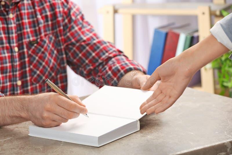 Autógrafo de firma del escritor en libro en la tabla, fotografía de archivo