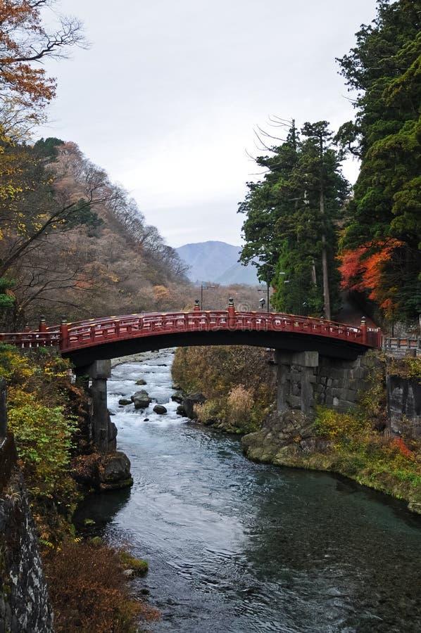Aut围拢的古老日本红色弧桥梁横穿小河 免版税库存图片