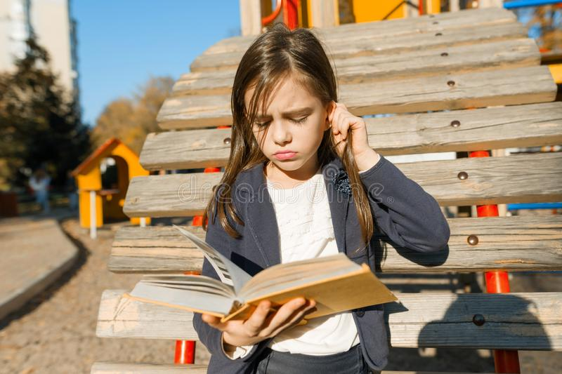 Autdoor portrait of offended little girl. A girl is reading thick book, offendedly pouting her lips royalty free stock photo