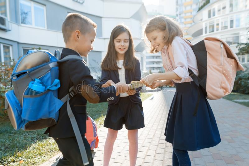 Outdoor portrait of smiling schoolchildren in elementary school. A group of kids with backpacks are having fun, talking. Education royalty free stock photo