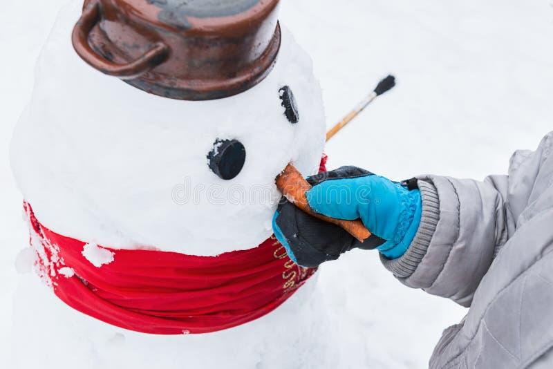 Autentisk familjvintergyckel Ungt barn som bygger en snögubbe Frank verklig folklivsstilbild av framställning av en snögubbe royaltyfria bilder