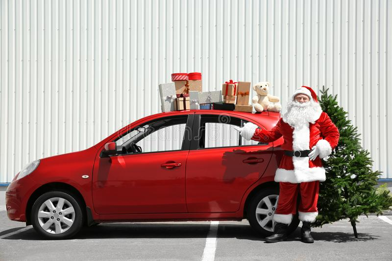Autentisk jultomten nära den röda bilen med gåvaaskar på den överkant för ` s royaltyfria bilder