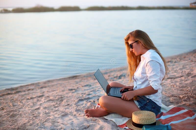 Autentyczna kobieta pracuje z laptopem na dennym brzeg Freelancer dziewczyny telecommuting z drużyną na projekcie na tropikalnej  zdjęcie royalty free