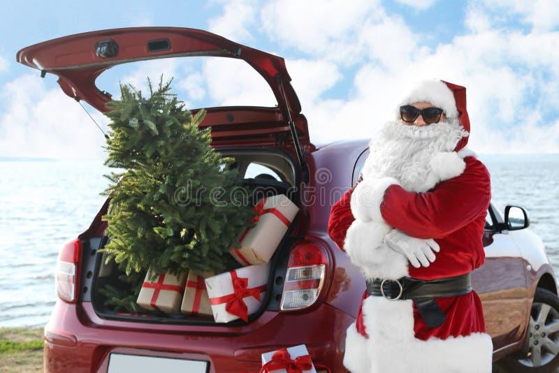 Autentyczny Święty Mikołaj blisko czerwonego samochodu z prezentem i choinką na plaży obrazy stock