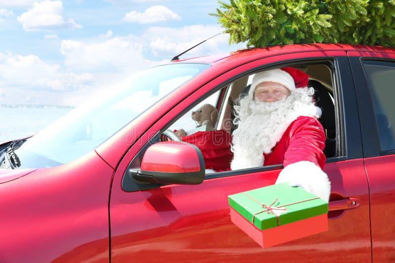 Autentyczny Święty Mikołaj mienia prezenta pudełko podczas gdy siedzący w samochodzie zdjęcie royalty free