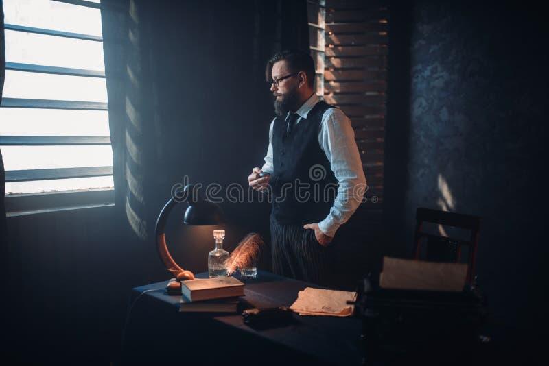 Auteur barbu en verres fumant une cigarette photo libre de droits