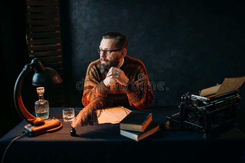 Auteur barbu en verres se reposant à la table images stock