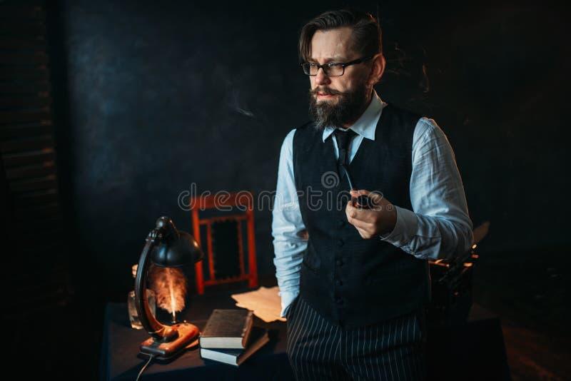 Auteur barbu sérieux en verres fumant un tuyau image libre de droits