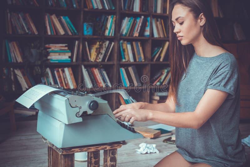 Auteur de jeune femme dans le détective créatif d'écriture de profession de bibliothèque à la maison image libre de droits