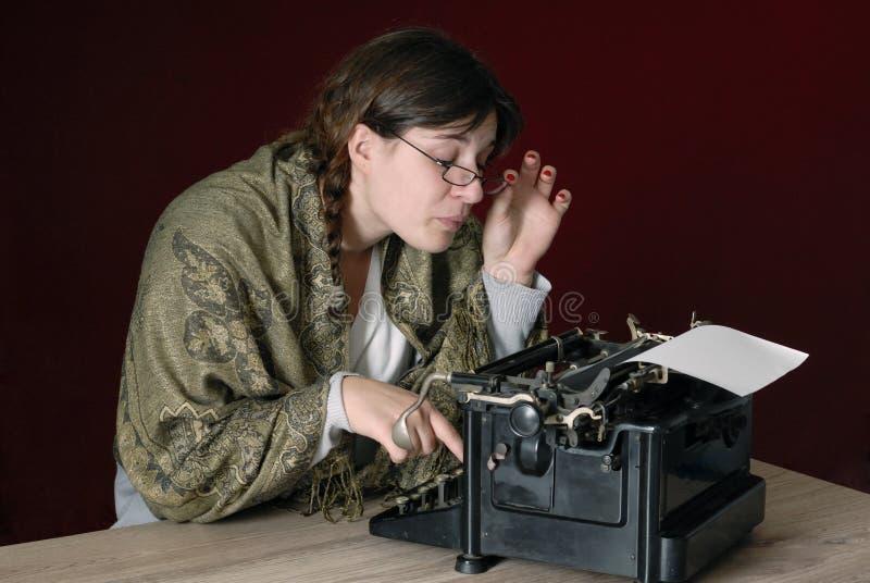 Auteur féminin tapant sur une vieille machine à écrire image stock