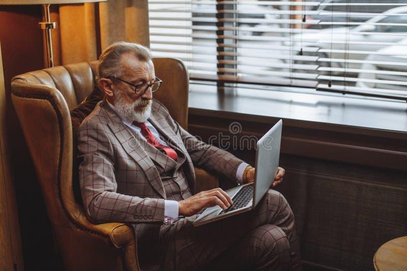 Auteur masculin plus âgé à la mode portant le travail élégant de vêtements images libres de droits