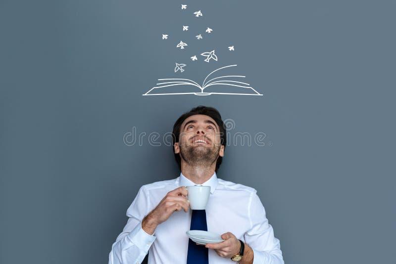 Auteur positif obtenant l'inspiration tout en buvant du café savoureux image stock