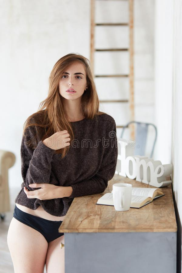 Authentic and attractive young woman looks towards the camera and grabs her hair royalty free stock photography
