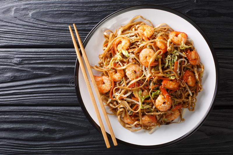 Authentic chow mein noodle fried with shrimp, vegetables and sesame seeds close-up on a plate. Horizontal top view. Authentic chow mein noodle fried with shrimp stock photo
