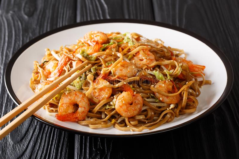 Authentic chow mein noodle fried with shrimp, vegetables and sesame seeds close-up on a plate. horizontal. Authentic chow mein noodle fried with shrimp royalty free stock images