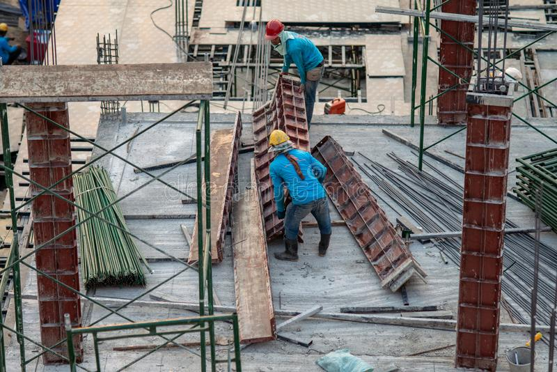 Authentic construction worker busy on the positioning of formwork frames in construction site. Aerial view of construction worker in construction site stock image