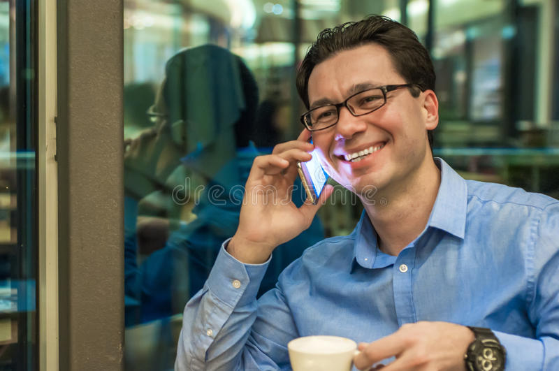 Authentic image of a businessman working in a cafe. Man talking on the mobile phone in a coffee shop.  stock photos