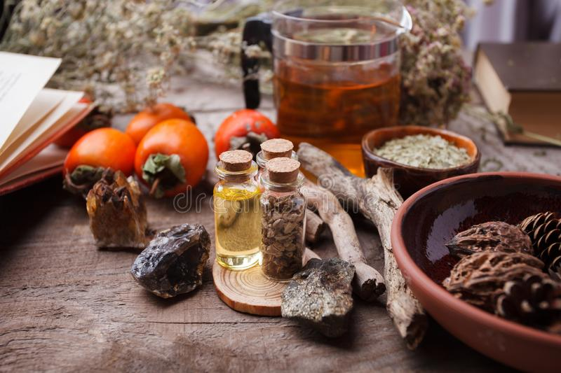 Bottles with herbs, dry flowers, stones and magic objects on witch wooden table. royalty free stock photo