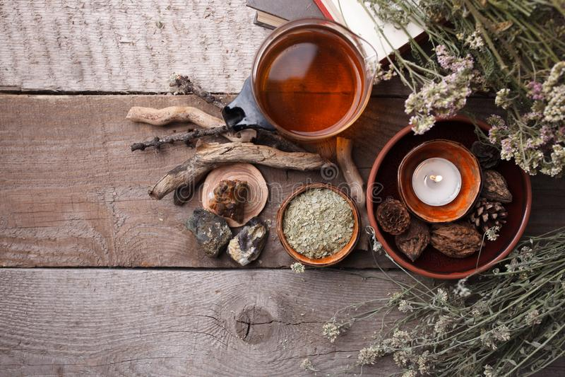 Authentic interior details, glass of herbal rea, homeopathic treatment on rustic wooden background top view, alternative medicine. Healthy closeup stock photos