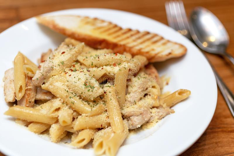 Authentic Italian creamy chicken Alfredo penne pasta in a restaurant closeup.  stock images