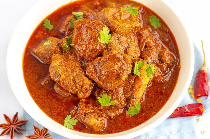 Authentic Lamb Vindaloo Traditional Fiery Red Indian / Goan Curry of Lamb. Lamb Curry / Lamb Vindaloo in a Bowl on White Background Close Up Photo royalty free stock image