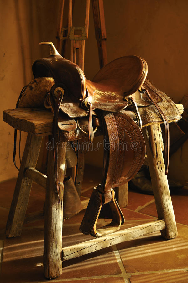 Authentic Leather Saddle. Authentic brown leather saddle for Western style horseback riding sitting on rustic wooden bench in morning light stock images