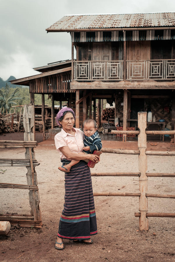 Authentic life of hill tribe from Myanmar. Loikaw, Myanmar - May 25, 2016: Woman from remote village in Myanmar standing with child near the traditional house stock image
