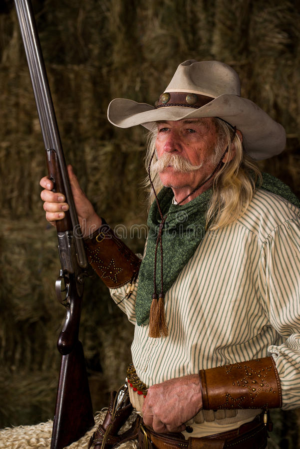 Authentic old west cowboy with shotgun, hat and bandanna in stable portrait royalty free stock photography