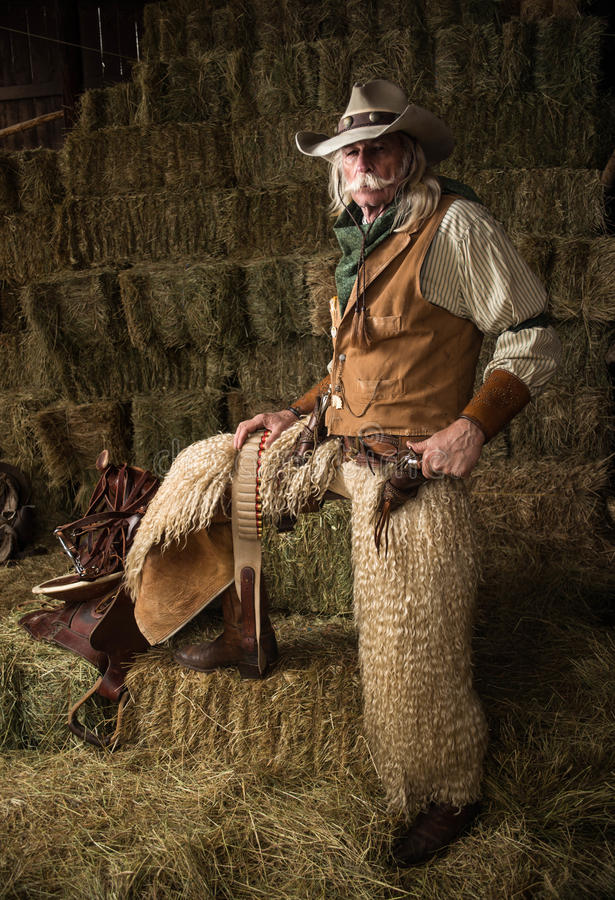 Authentic old west cowboy with shotgun, hat and bandanna in stable portrait. In a barn stock photo