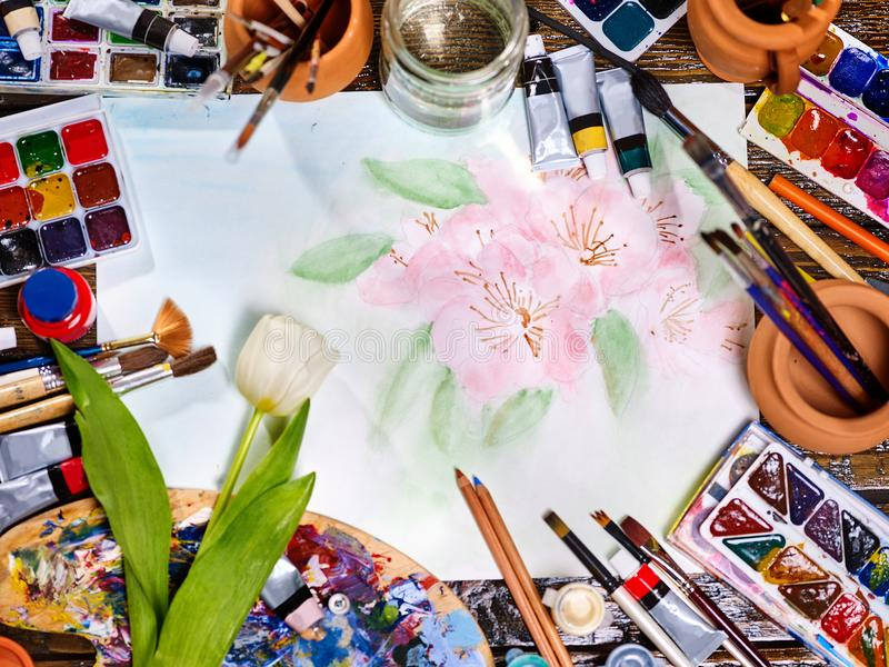 Authentic paint brushes still life on table in art class school. Authentic paint brushes still life in art class school. Group of brush in clay jar. Bouquet of stock images