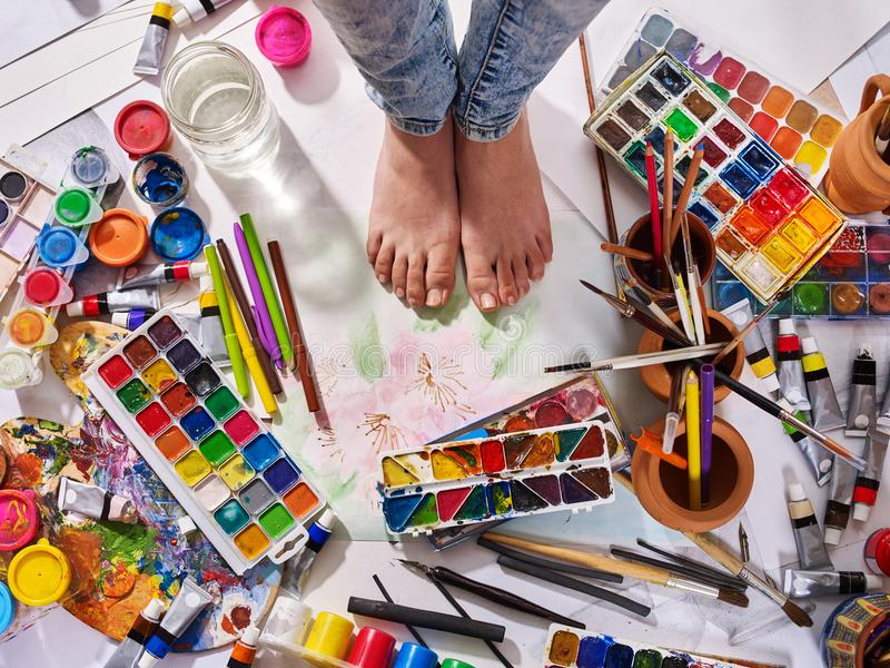 Authentic paint brushes still life on floor in art class school. Group of brush in clay jar. Barefooted female feet among creative mess stock photography