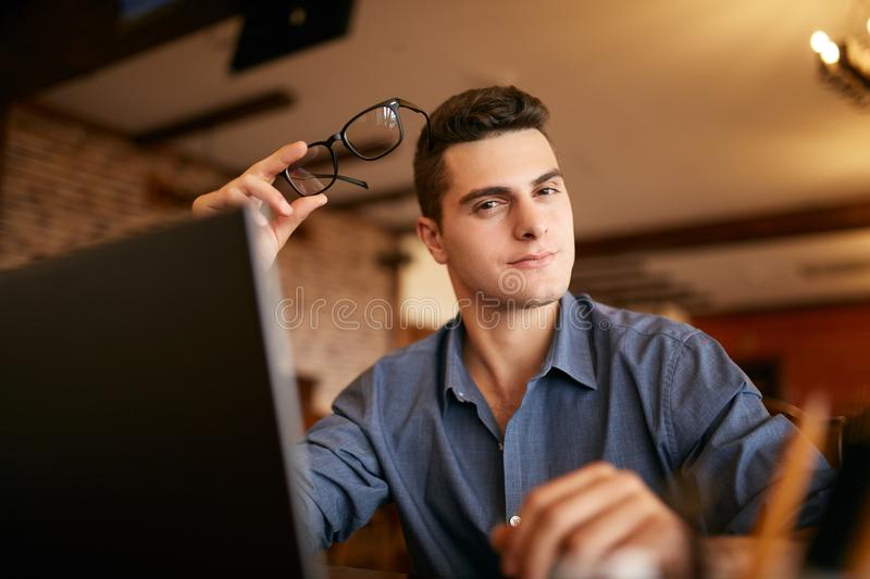 Authentic portrait of young confident businessman looking at camera with laptop in office. Hipster with in glasses and stock images