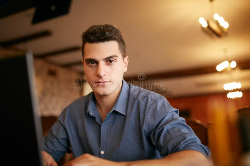 Authentic portrait of young confident businessman looking at camera with laptop in office. Hipster man and knitted stock photos