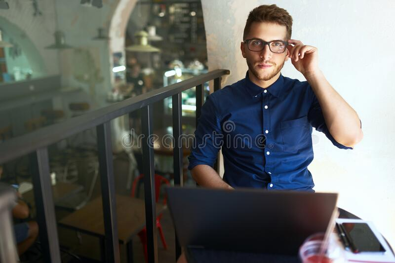 Authentic portrait of young confident businessman looking at camera with laptop in office. Hipster man in glasses doing royalty free stock photos