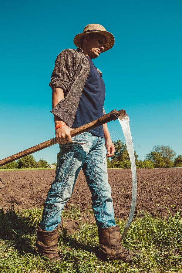 Authentic rural farmer with scythe. Agriculture worker. Farm implements. Rustic background. Work countryside. Brutal country man. Manual labor. European royalty free stock image
