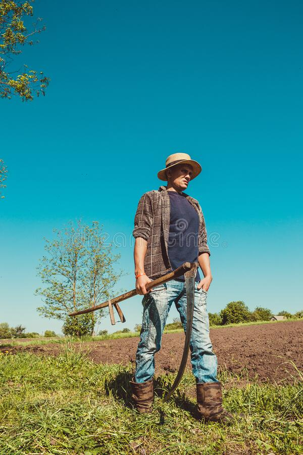 Authentic rural farmer with scythe. Agriculture worker. Farm implements. Rustic background. Work countryside. Brutal country man. Manual labor. European stock photo