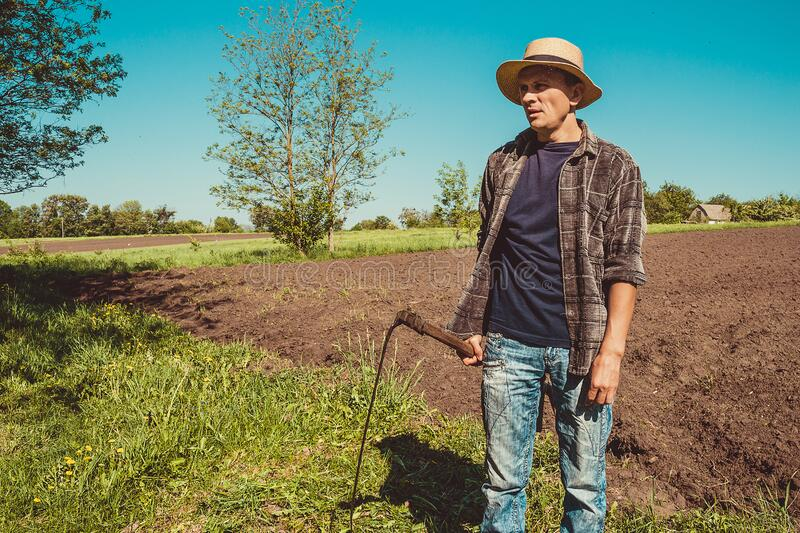 Authentic rural farmer with scythe. Agriculture worker. Vegetable garden. Farm implements. Rustic background. Work countryside. Brutal country man. Manual royalty free stock photography