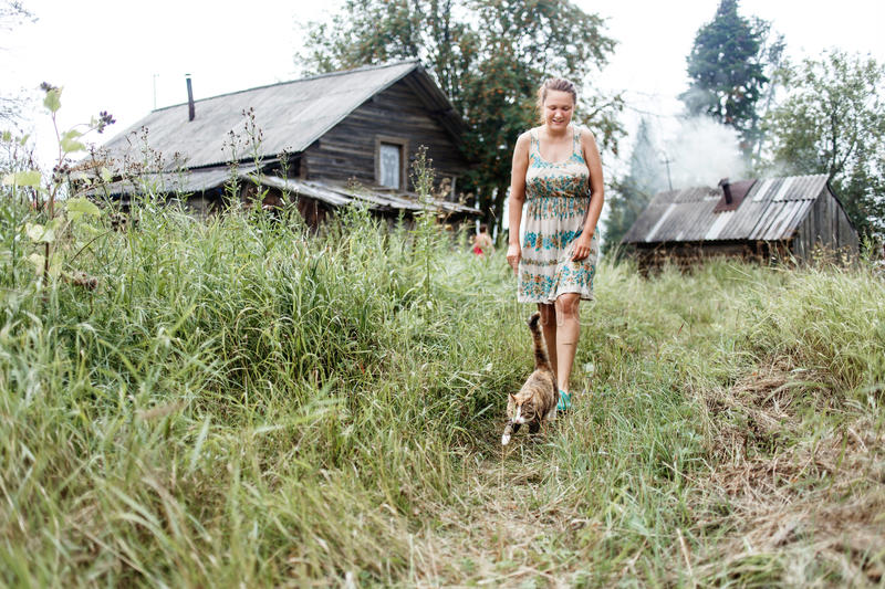 Authentic rural picture of walking cat, woman, and old log house with heating bath stock photos